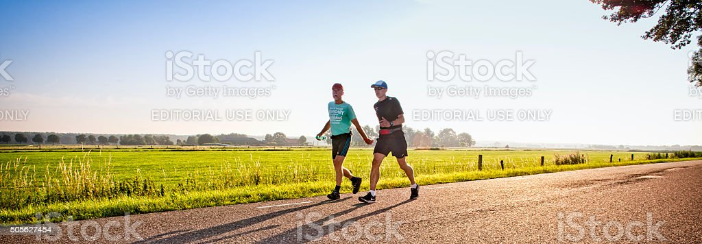 Two lonely walkers on the International Four Days Marches Nijmeg stock photo