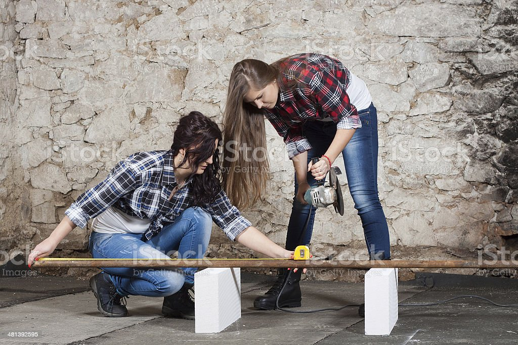 Two long-haired young woman with an angle grinder stock photo