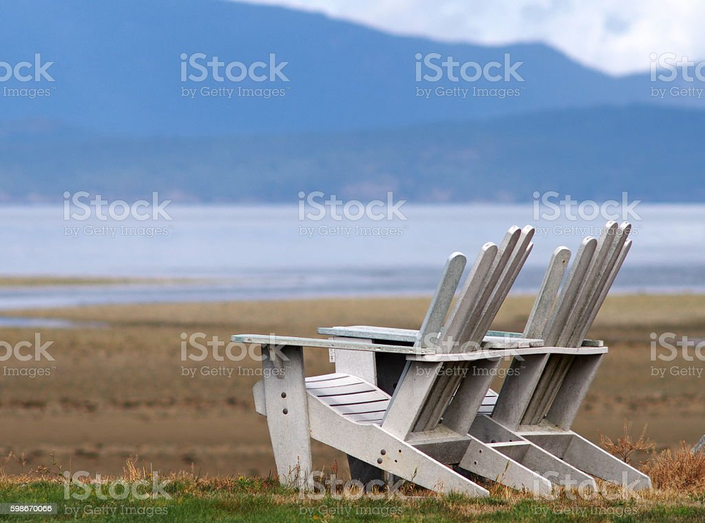 Two Lounge Chairs on a Beach with Mountains stock photo