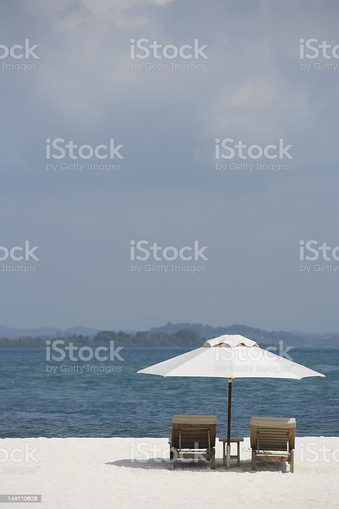two lounge chairs on white sand beach stock photo