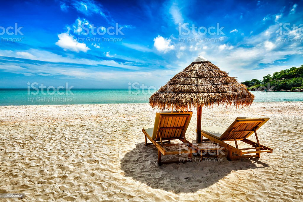 Two lounge chairs under tent on beach stock photo
