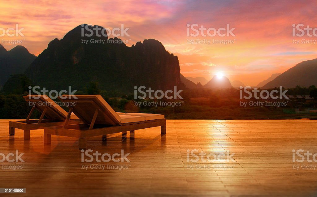 Two lounge chairs with a tropical mountain landscape at sunset stock photo