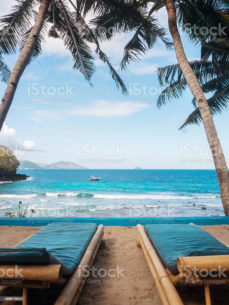 Two loungers on a tropical beach in front of water stock photo