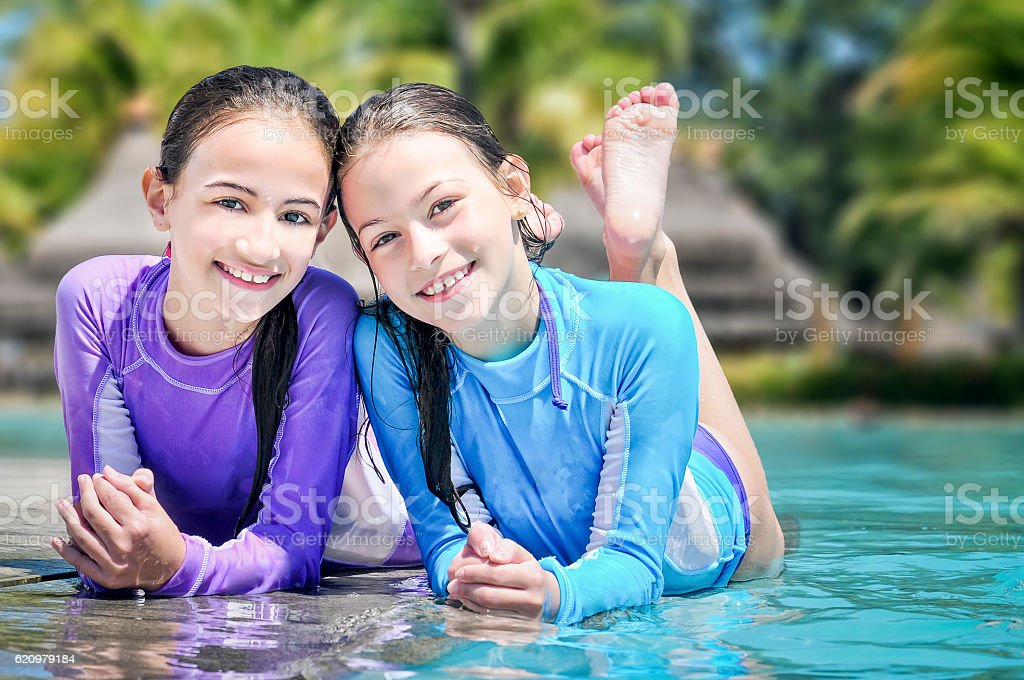 Two Lovely Sisters Enjoying Summer by the Pool stock photo