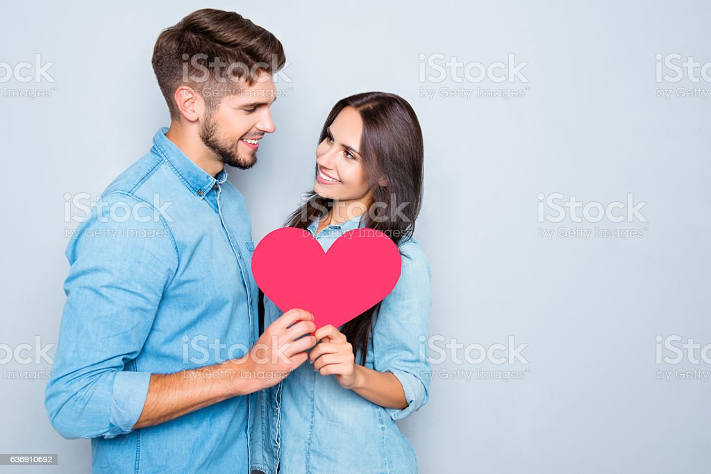 Two lovers holding paper heart on gray background stock photo