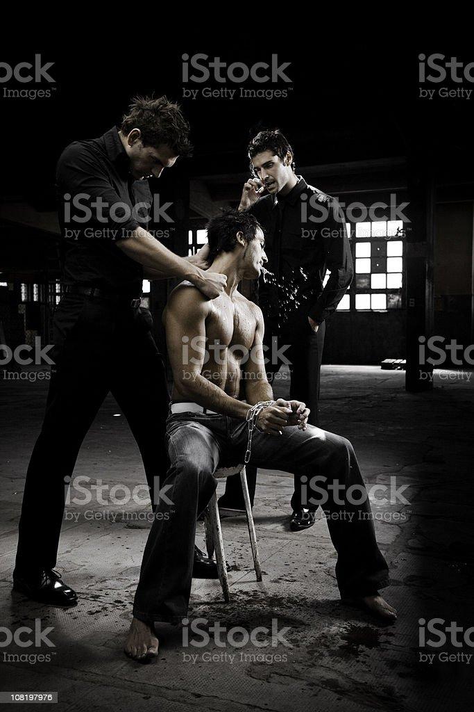 Two Mafia Men Beating Up Handcuffed and Captive Man royalty-free stock photo