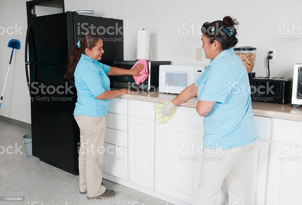 Two maids cleaning a corporate break room stock photo