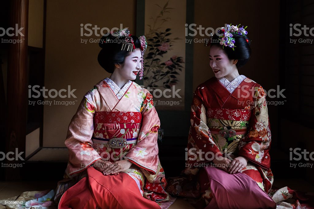 Two maiko geisha sitting in a room in Kyoto, Japan stock photo