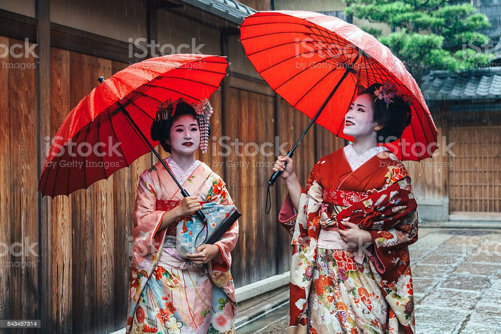 Two maiko geisha walking on a street in Kyoto, Japan stock photo
