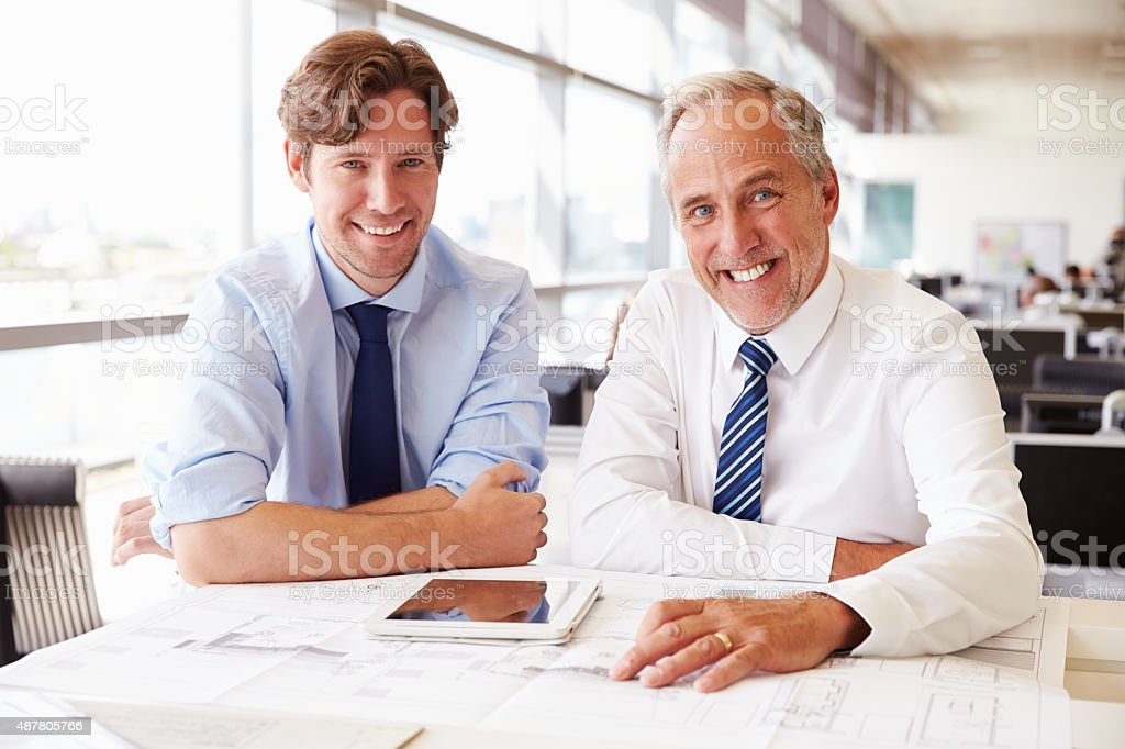 Two male architects working together, looking to camera stock photo
