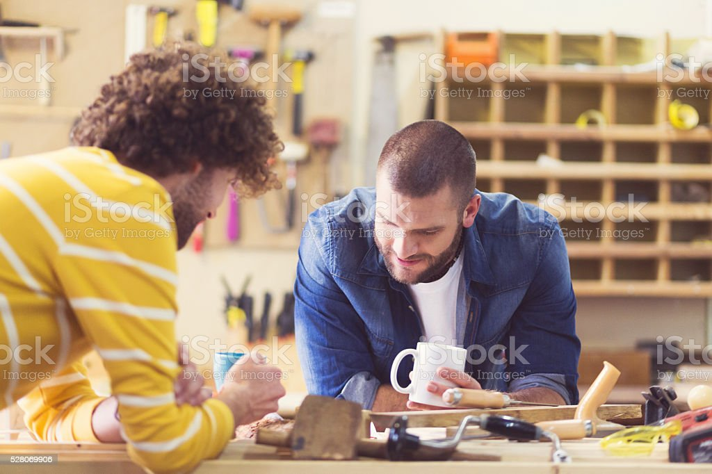 Two male carpenters in a construction workshop, working together stock photo