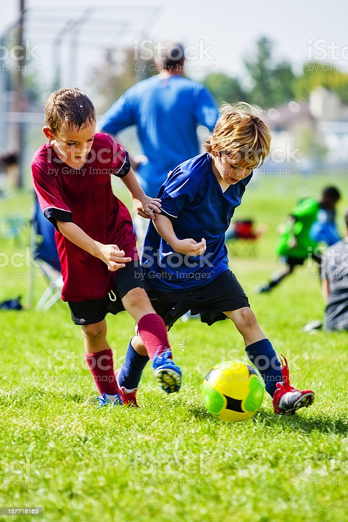 Two Male Children Compete in Soccer Kicking Battle for Ball royalty-free stock photo