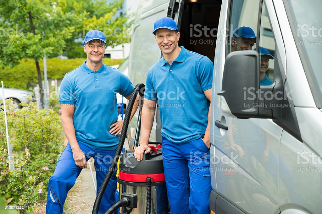 Two Male Cleaners With Vacuum Cleaner stock photo