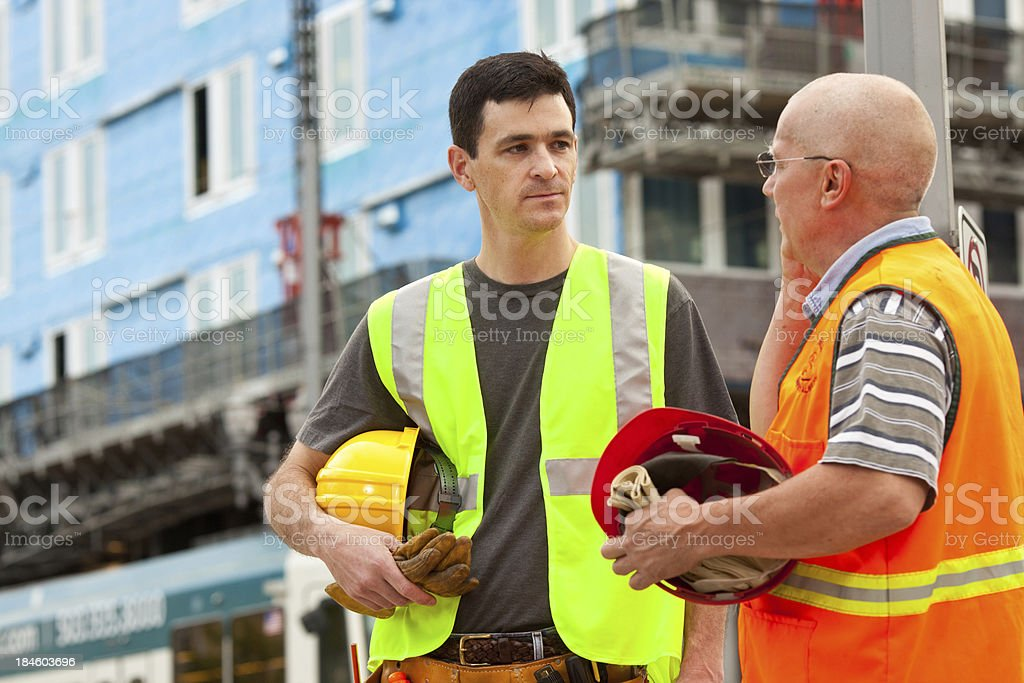 Two Male Construction Workers holding hard hats. royalty-free stock photo