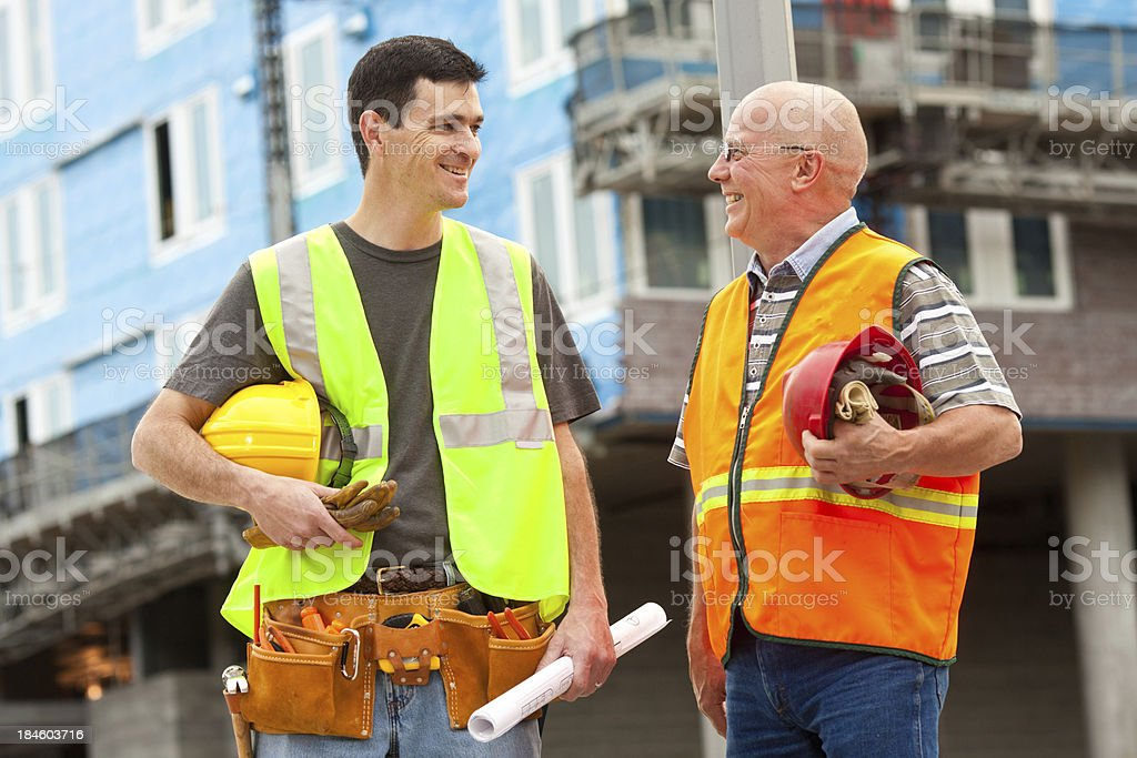 Two Male Construction Workers Looking At Each Other royalty-free stock photo