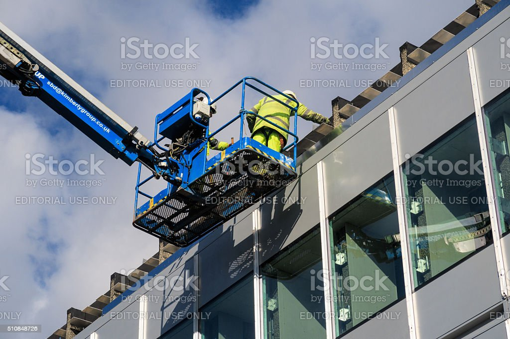 Two male construction workers working at height stock photo