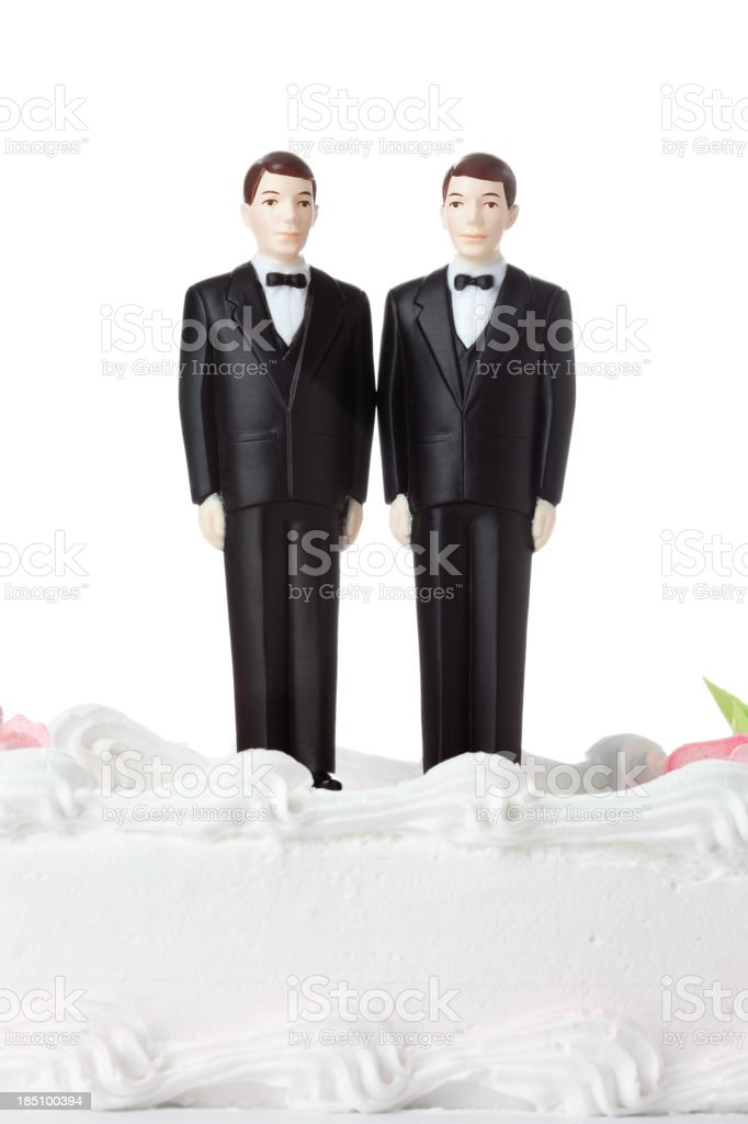 Two male figurines dressed in tuxedos atop a white cake stock photo