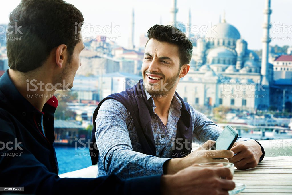 Two male friends discussing girls on a yacht in Istanbul stock photo