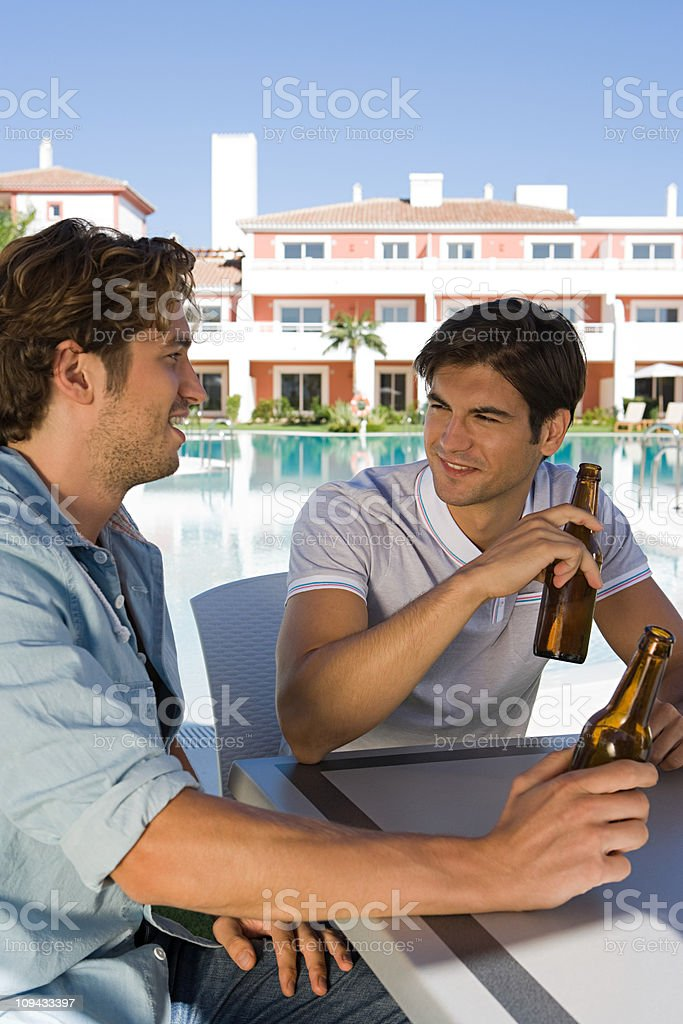 Two male friends enjoying beer on holiday stock photo