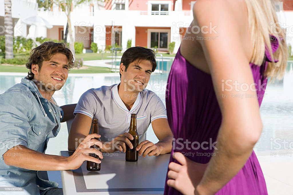 Two male friends flirting with woman on holiday stock photo