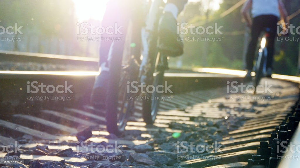 Two male friends riding bicycles on the rail track in foto de stock libre de derechos