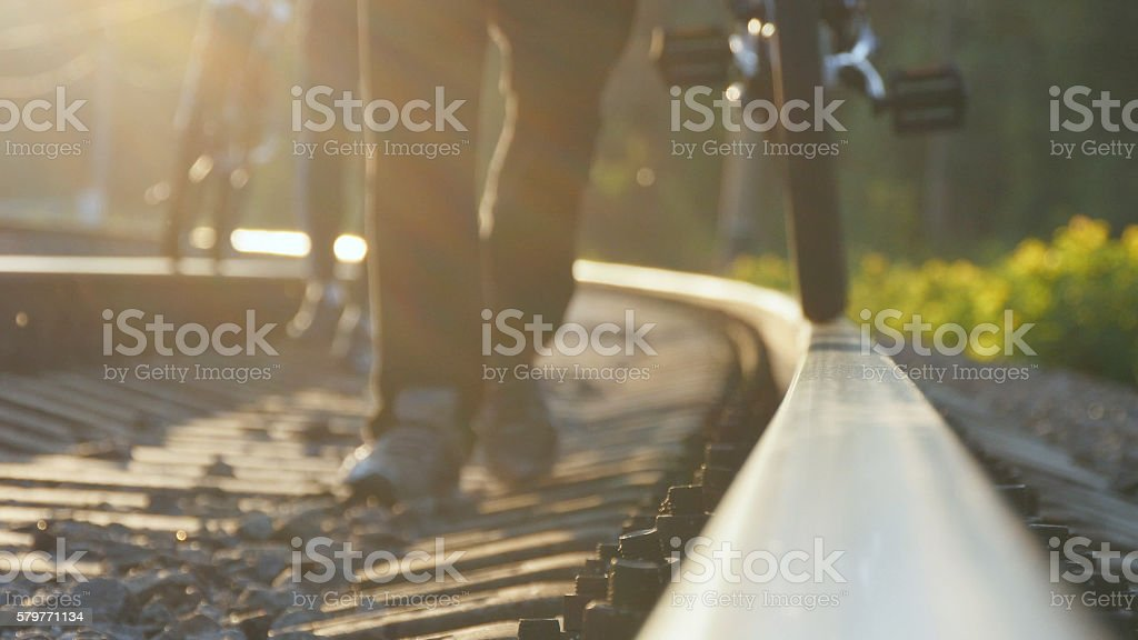 Two male friends walking with their bikes on the rails foto de stock libre de derechos