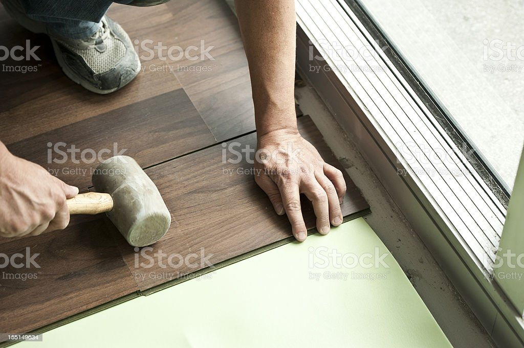 Two male hands holding mallet installing hardwood floor. stock photo