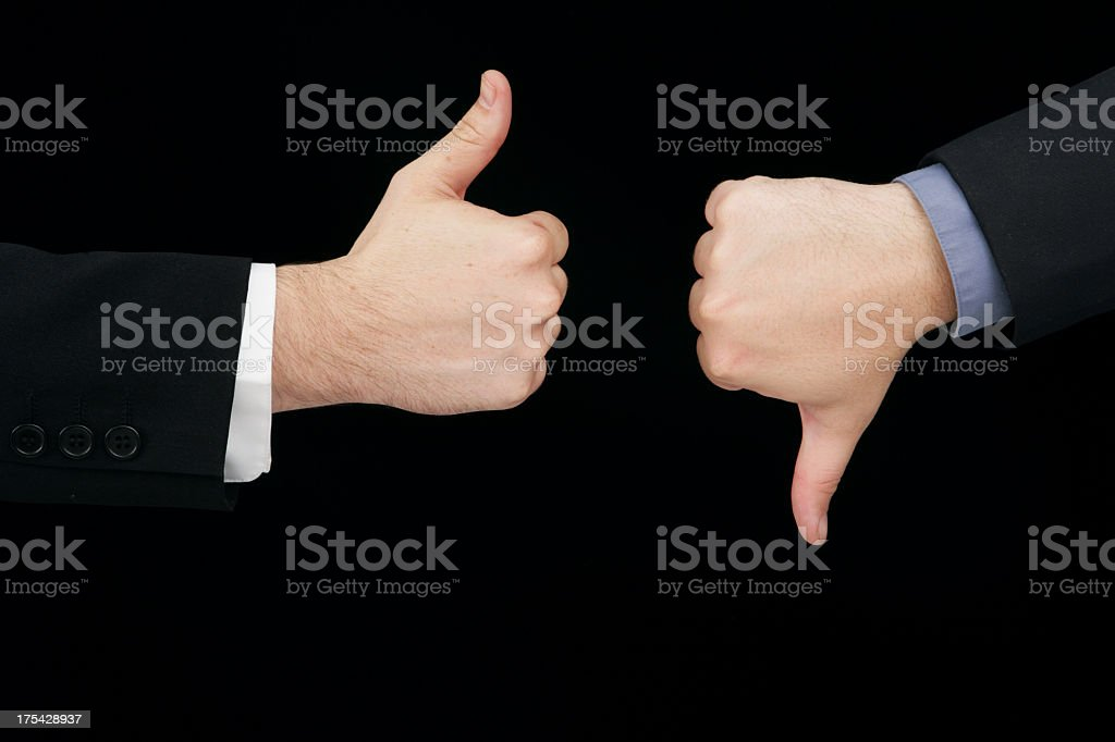 Two male hands offering a thumbs up and thumbs down stock photo