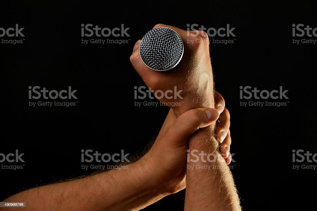 Two male hands with microphone isolated on black royalty-free stock photo