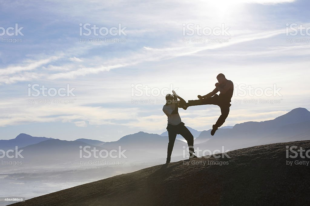 Two male kickboxers fighting on a mountain top royalty-free stock photo
