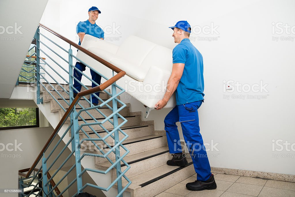 Two Male Movers Carrying Sofa On Staircase stock photo