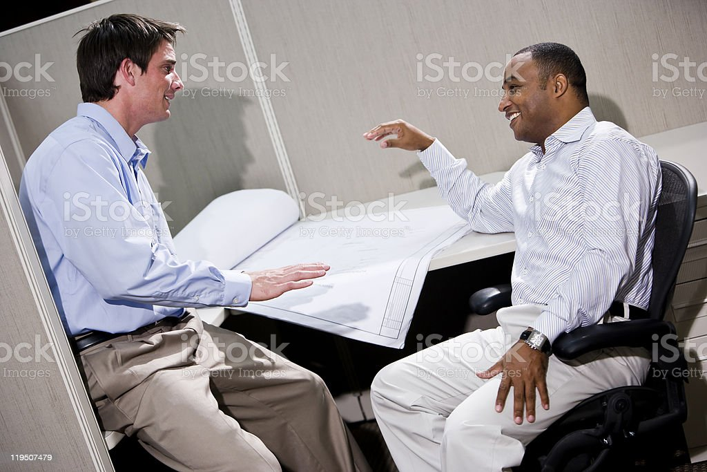 Two male office workers working in cubicle with blueprints royalty-free stock photo