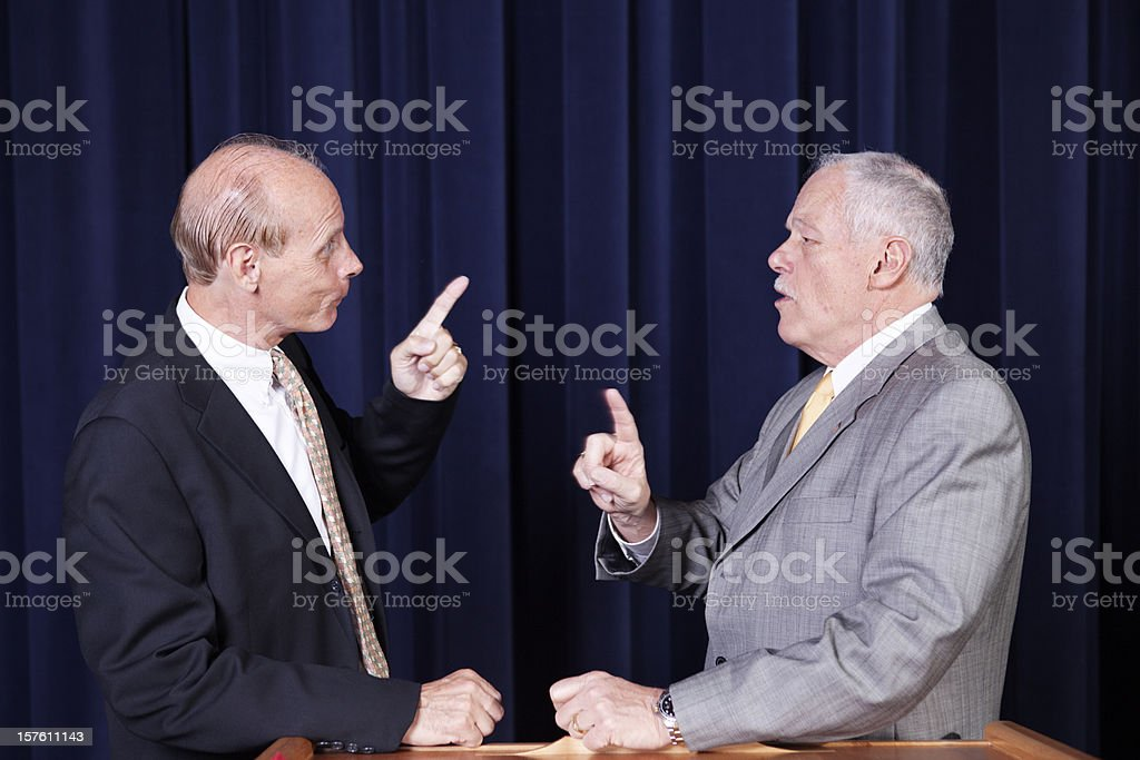Two male politicians arguing with accusations at a rally stock photo