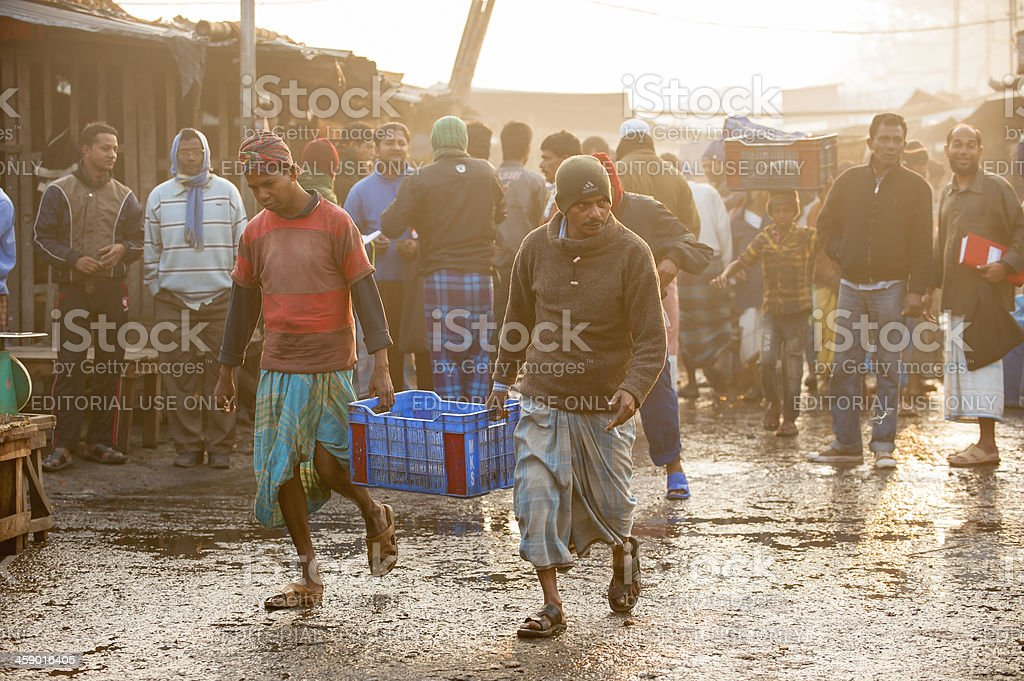 Two man carrying carton walking in fish market, Bangladesh stock photo