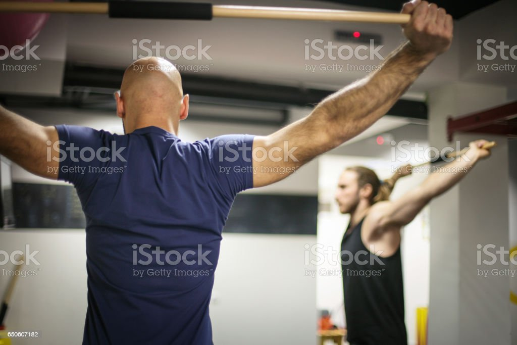 Two man doing stretching exercise in  gym. stock photo