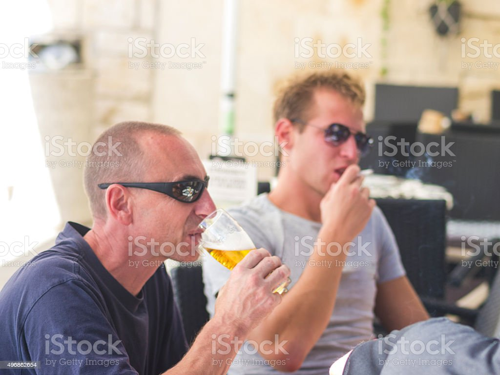 Two man, drinking and smoking in Komiza restaurant, Croatia stock photo