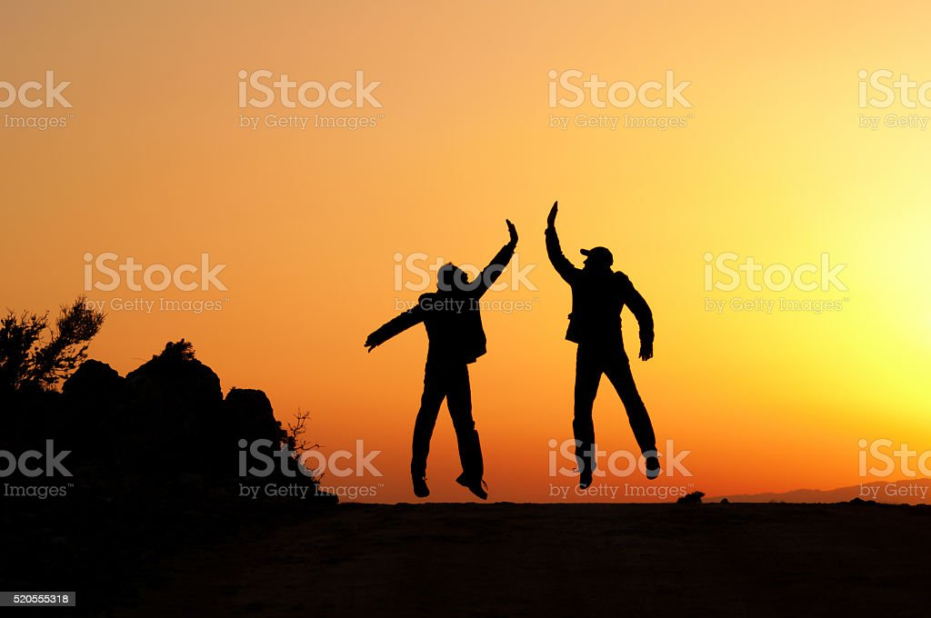 Two man holding for hands and jumping.They are successful people. stock photo