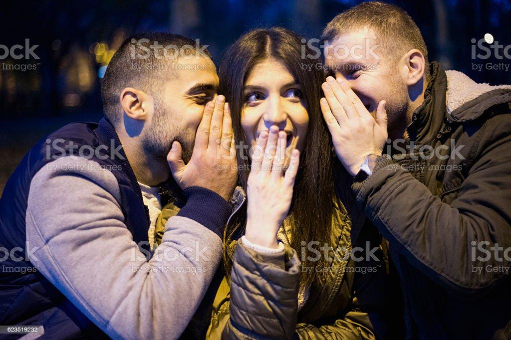 Two man whispering something shocking to girl stock photo