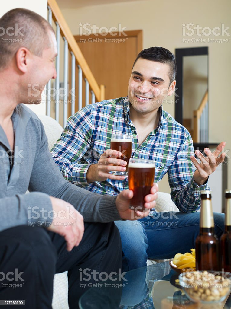 Two man with beer sit and talk stock photo