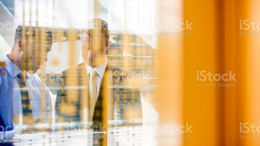 Two managers shot through glass wall stock photo