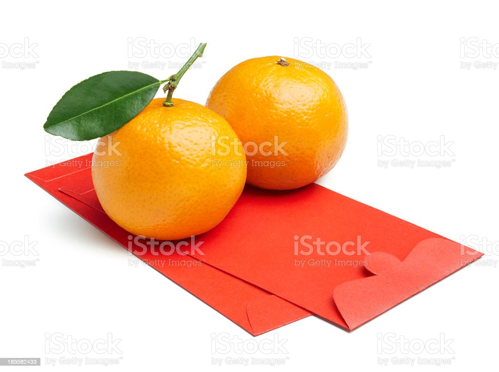 Two mandarin oranges sitting on red envelopes stock photo