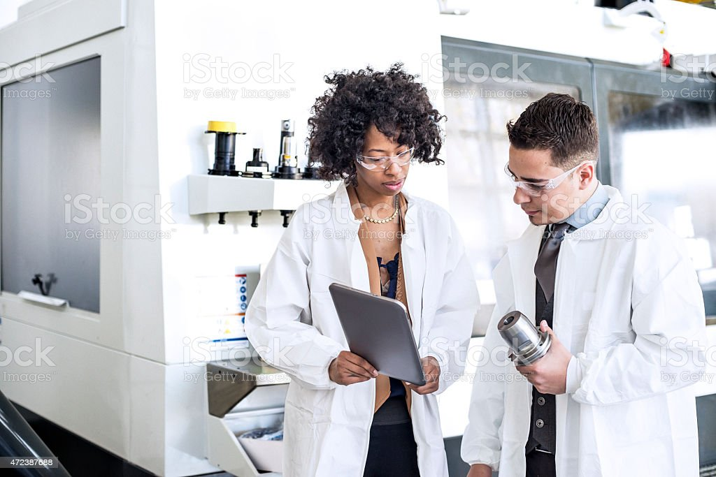 Two manufacturing engineers looking at tablet on a lab stock photo