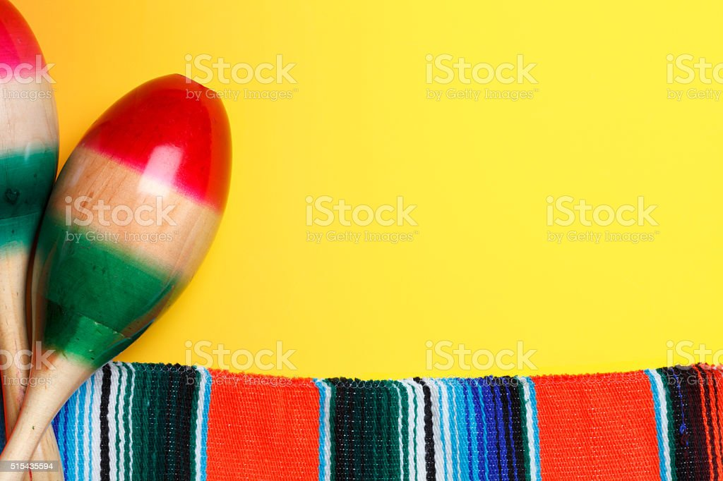 Two Maracas And A Mexican Blanket On A Bright Yellow Background stock photo