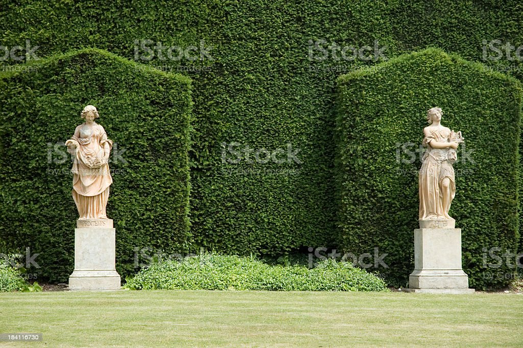 Two marble statues against hedges in an English garden stock photo