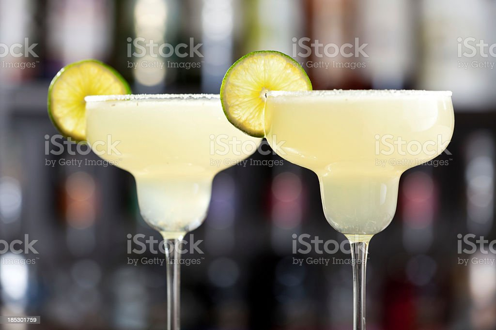 Two margaritas with lime wedges and salted glasses stock photo