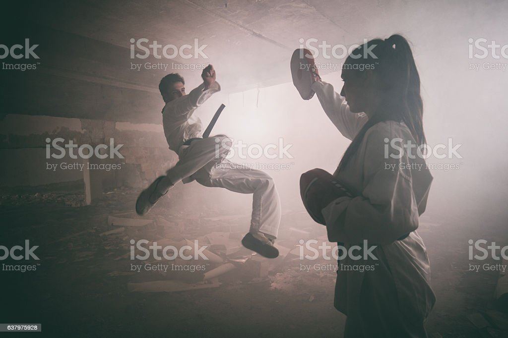 Two martial artists practicing together among ruins. stock photo