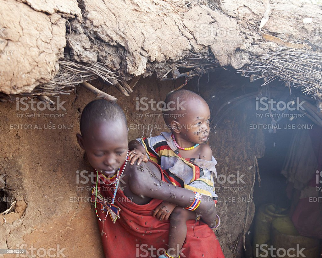 Two masai children outside the cow's dung hut. stock photo