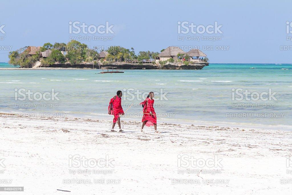 Two Masai warriors walking on the beach stock photo