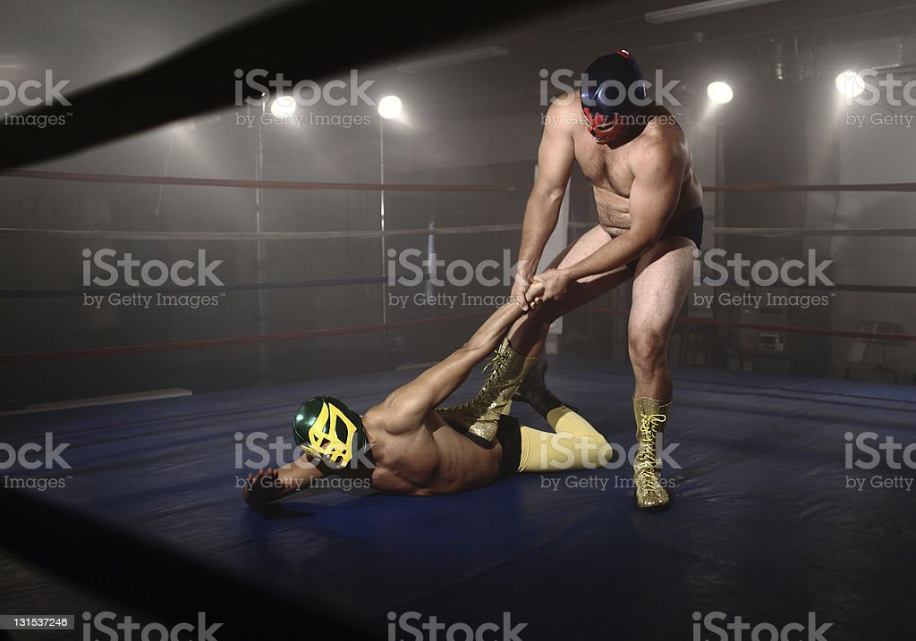 Two masked wrestlers fight in grungy ring stock photo