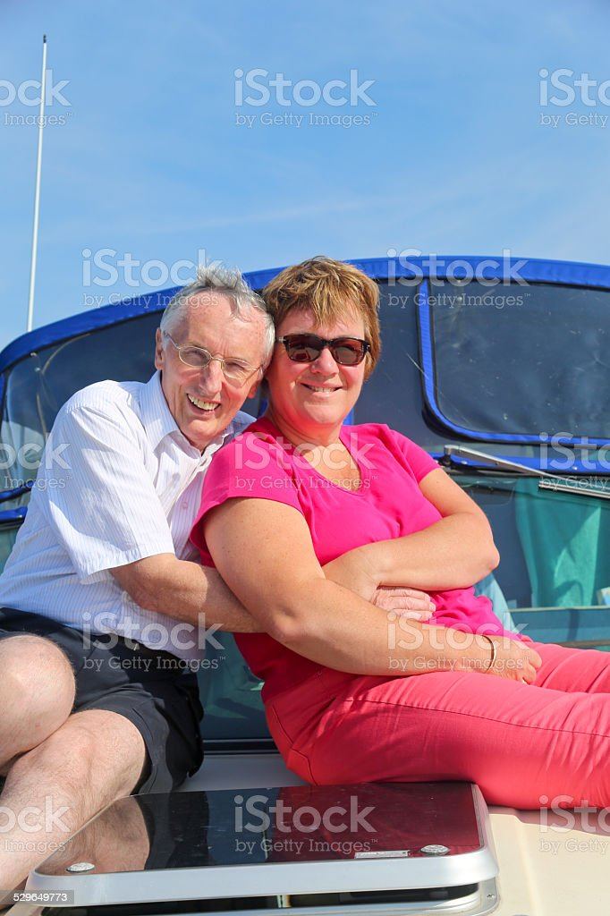 Two Mature Adults Hugging on a Yacht's Foredeck stock photo